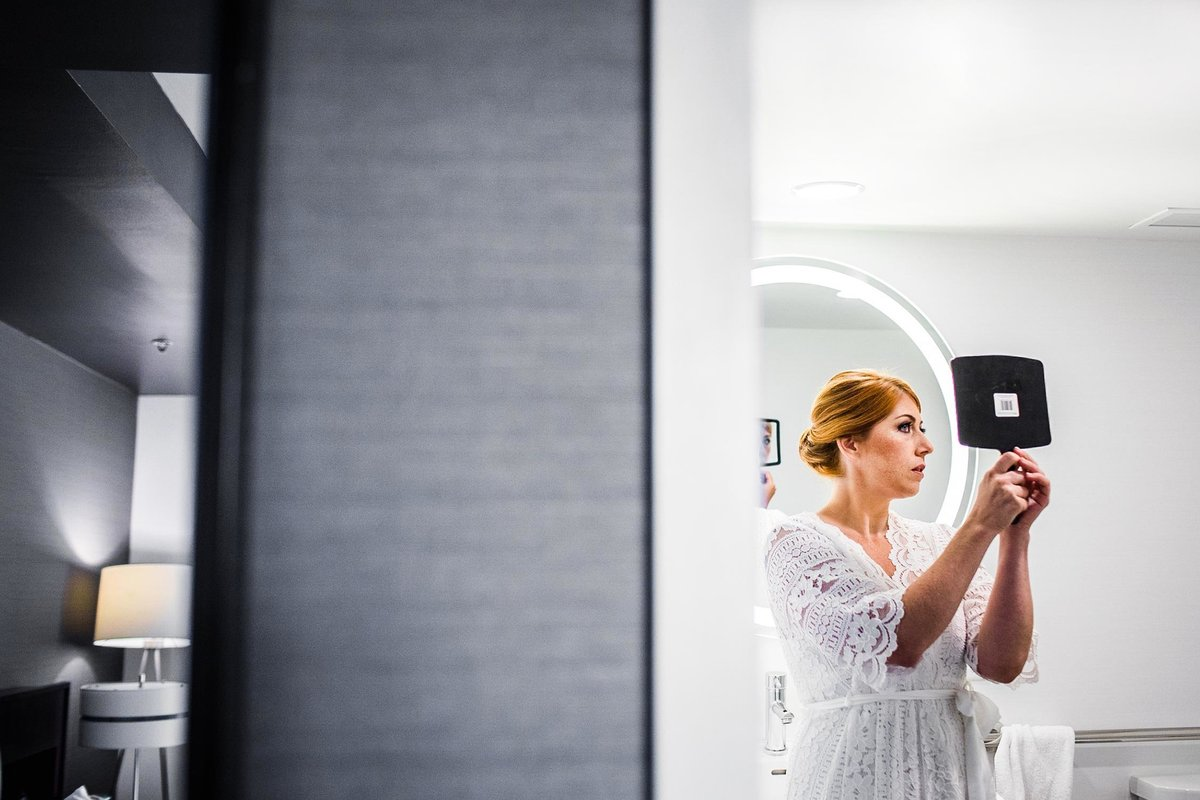 A bride checks herself out in a mirror before her Chicago wedding.