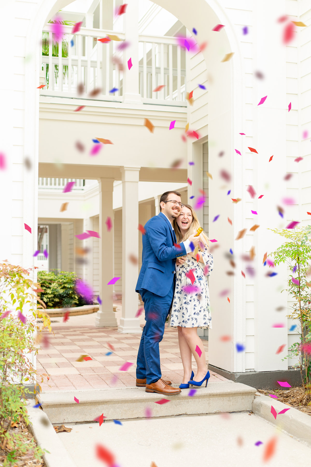 Tampa Florida husband and wife photography team celebrate with confetti champagne bottle with wife in white floral dress and husband in blue suit