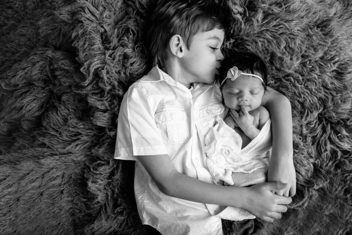 A big brother loves on his sister during her baby photoshoot