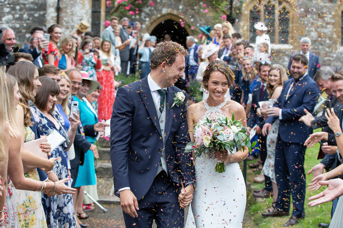 Bride and Groom with confetti at Huntsham Court Wedding Devon_