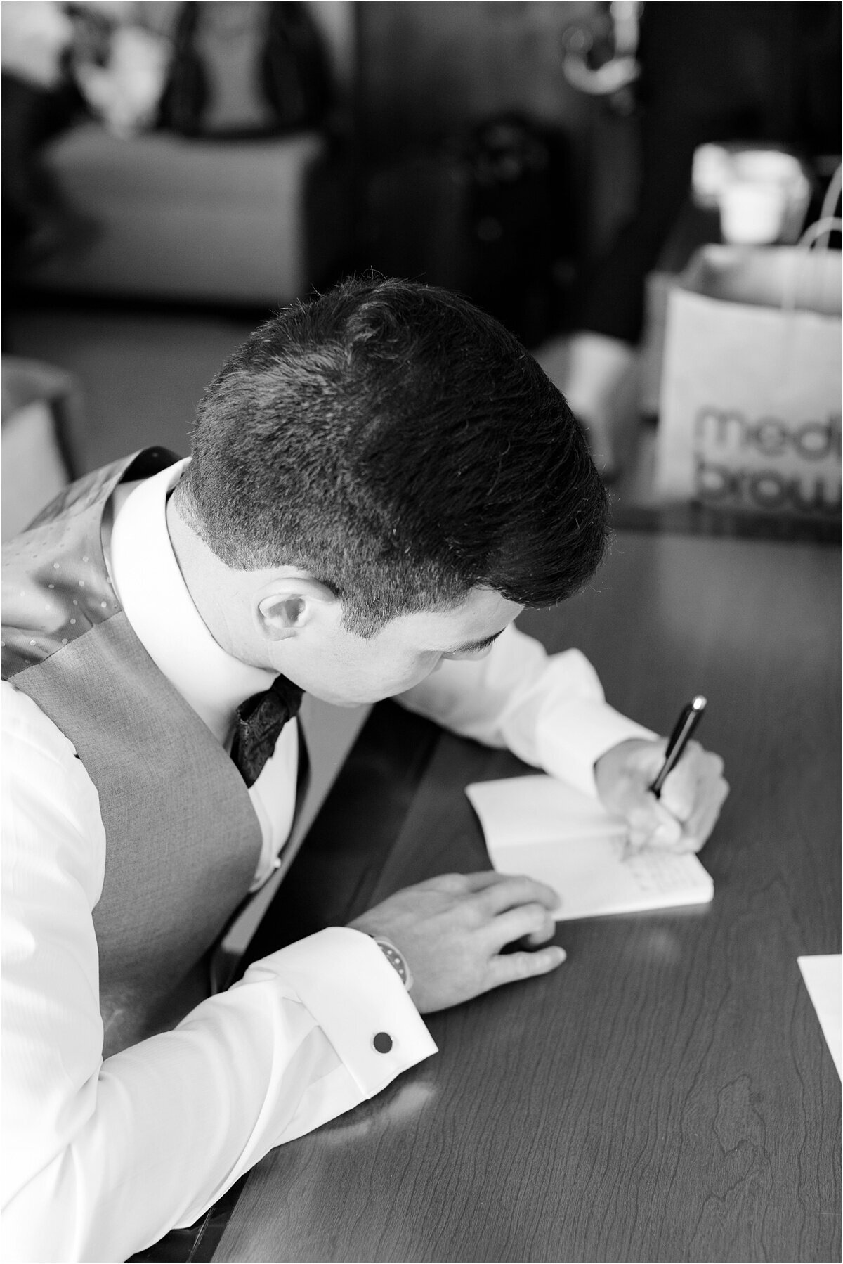 black and white image with groom writing his vows Monterey california