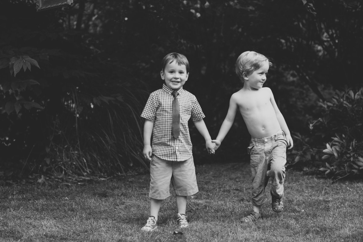 2 boys playing in the garden at a wedding holding hands