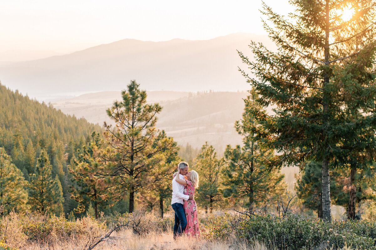 Couple kissing at sunset during engagement session on top of Echo Ridge Trail
