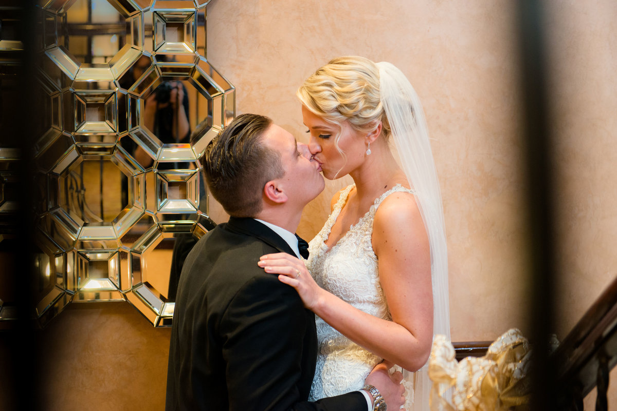 Bride and groom kissing on steps at The Inn at Fox Hollow