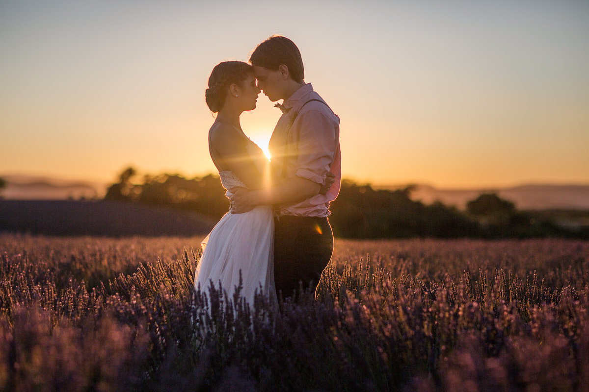 Sundet in the lavender fields of Provence, fance with a couple holding each other and kissing while the sun is lighting up the space between them