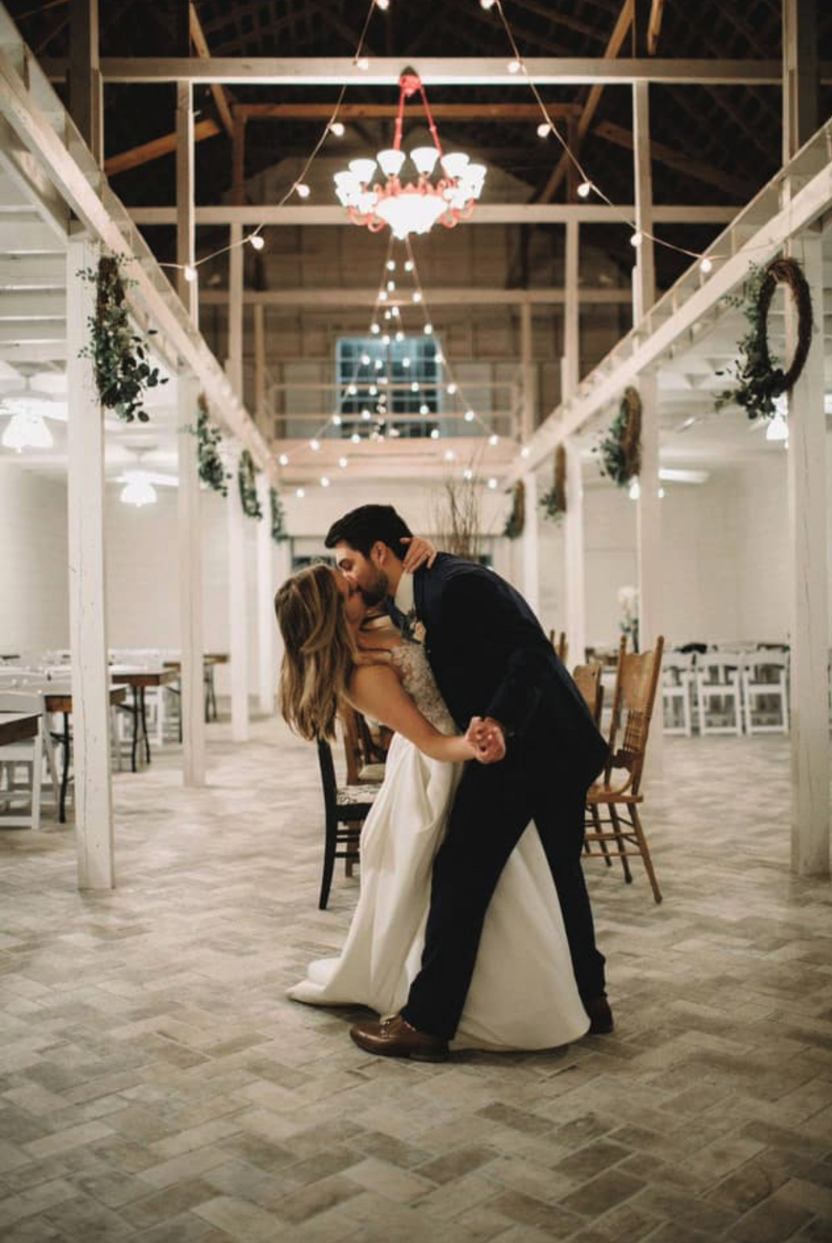 A bride and groom kissing during their last dance of the night in the Grand Texana's reception hall