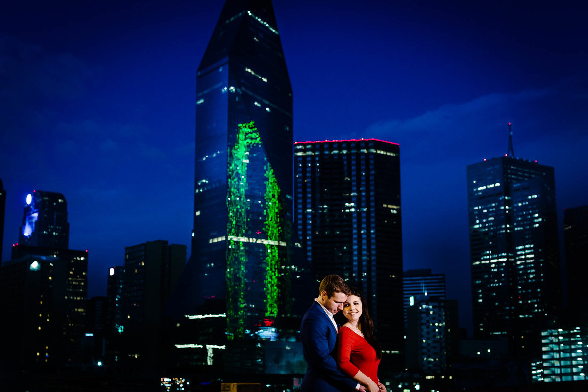 couple kissing in front of dallas skyline during their dallas engagament session