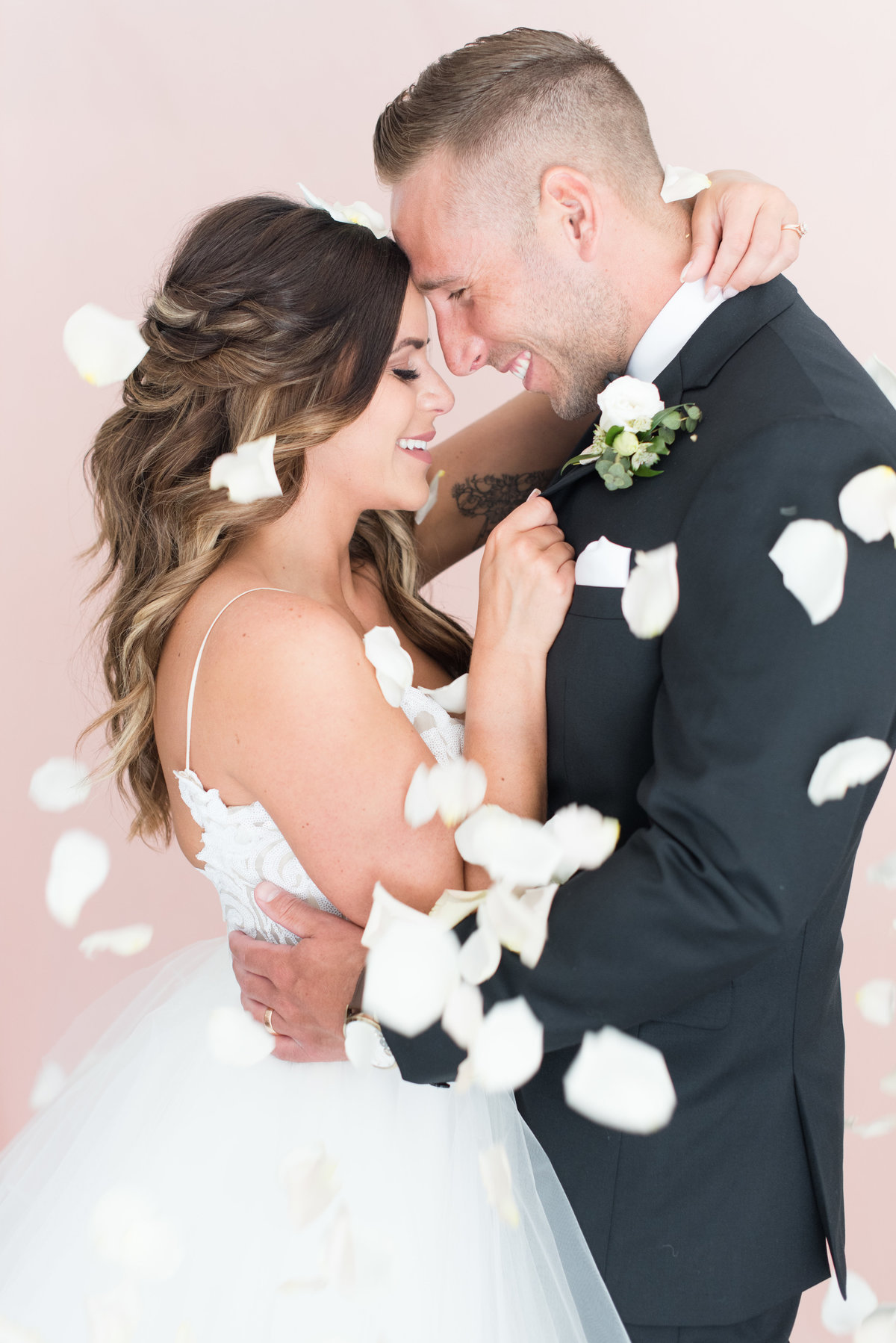 Bride and groom touch foreheads while being showered with white rose petals