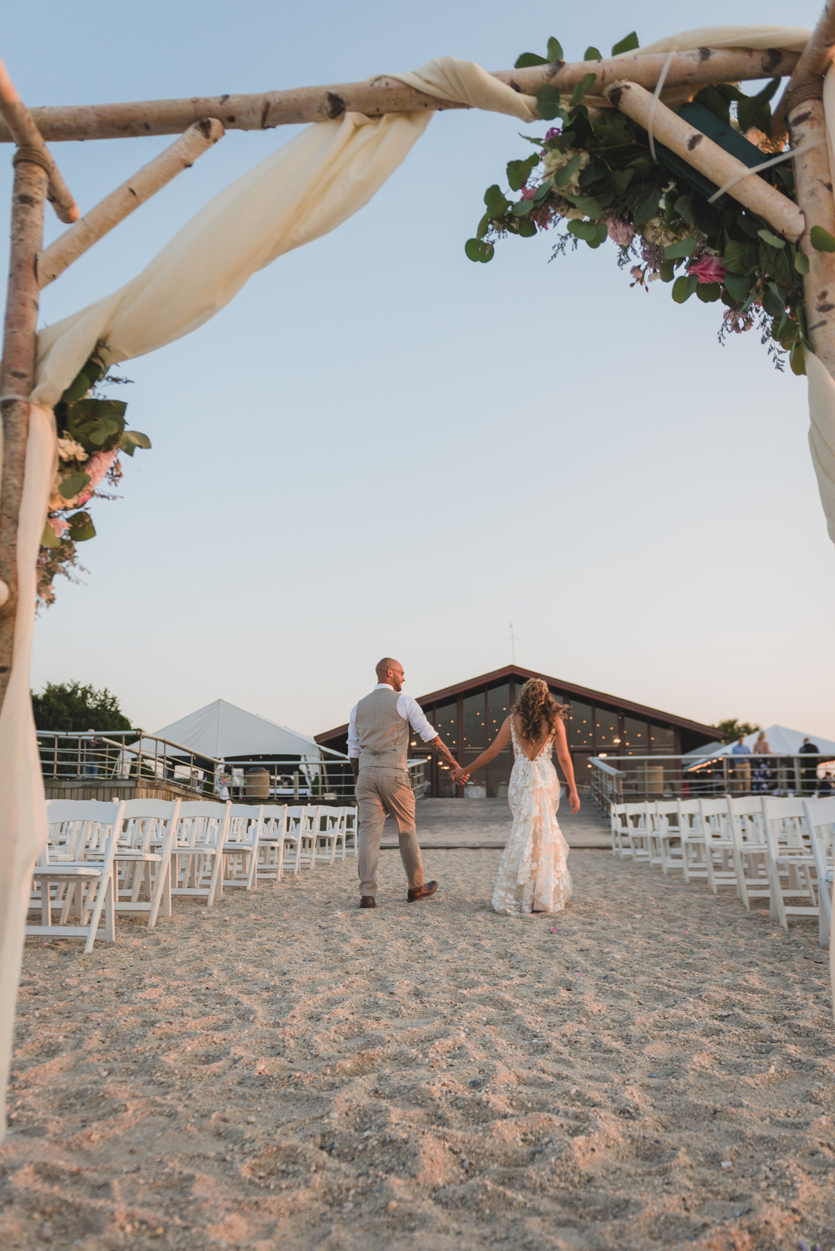 bride and groom walking on the beach for wedding at Pavilion at Sunken Meadow