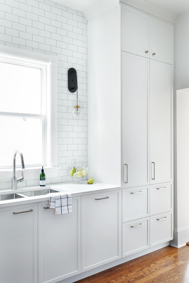 White kitchen cabinets - subway tiles - black sconces