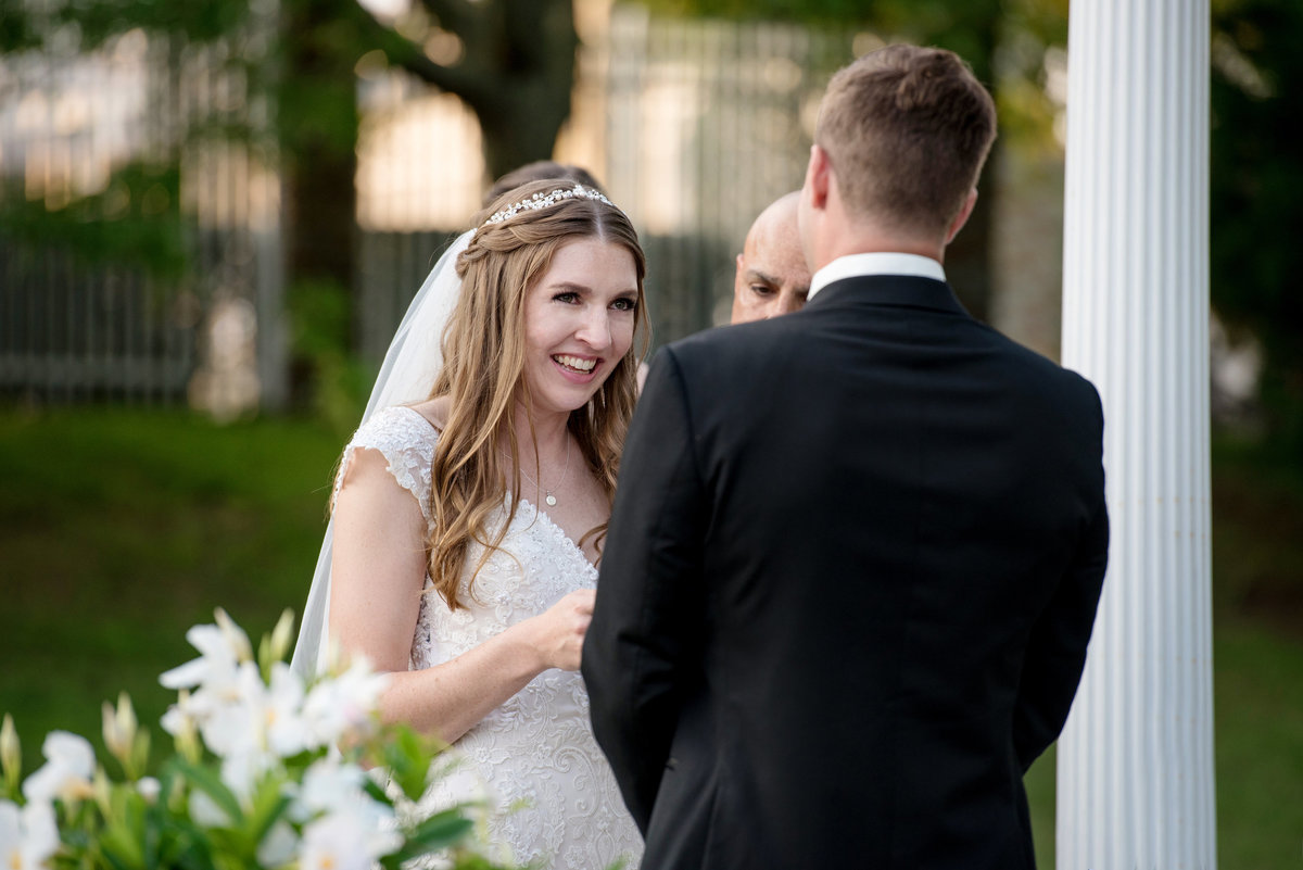 bride smiling at groom during outdoor wedding ceremony at Willow Creek Golf and Country Club