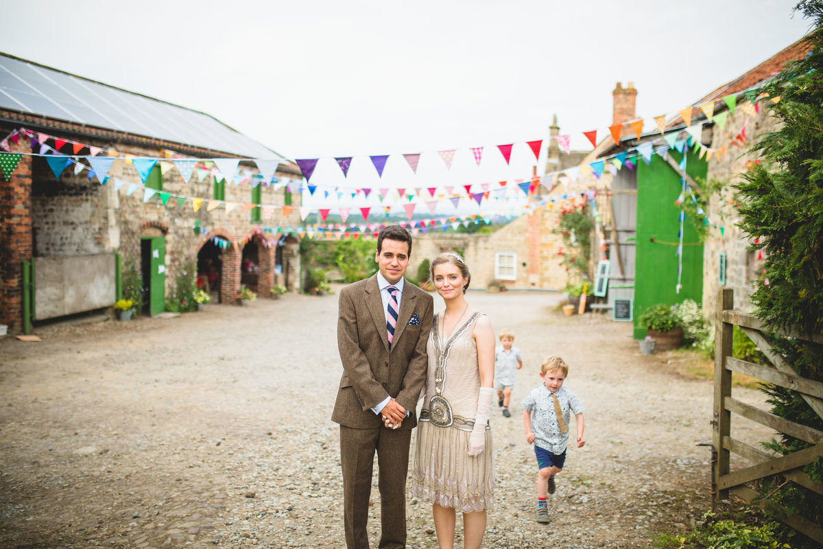 a vintage barn wedding at a farm with bunting and a whistles wedding dress