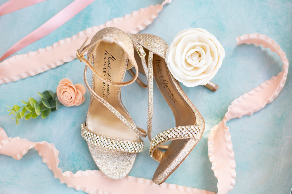 Badgley Mischka bridal shoes details from wedding day  with a blue backround blush ribbon and white flowers
