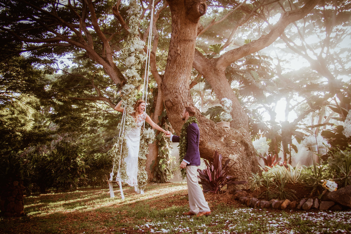 Bride and groom on a flower swing at Kauai wedding.