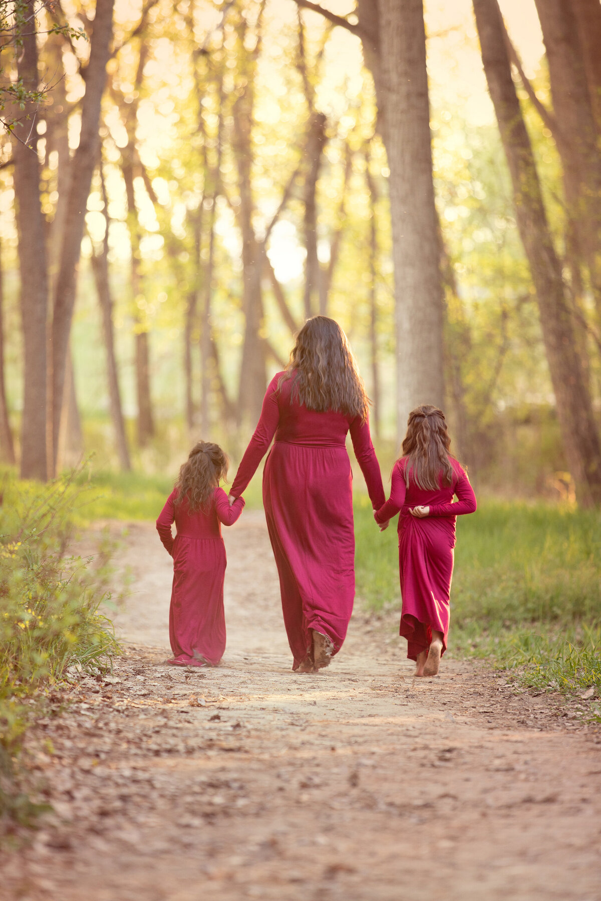 Mom and daughters wearing maroon dresses walking along path at river front park near the river at sunset.
