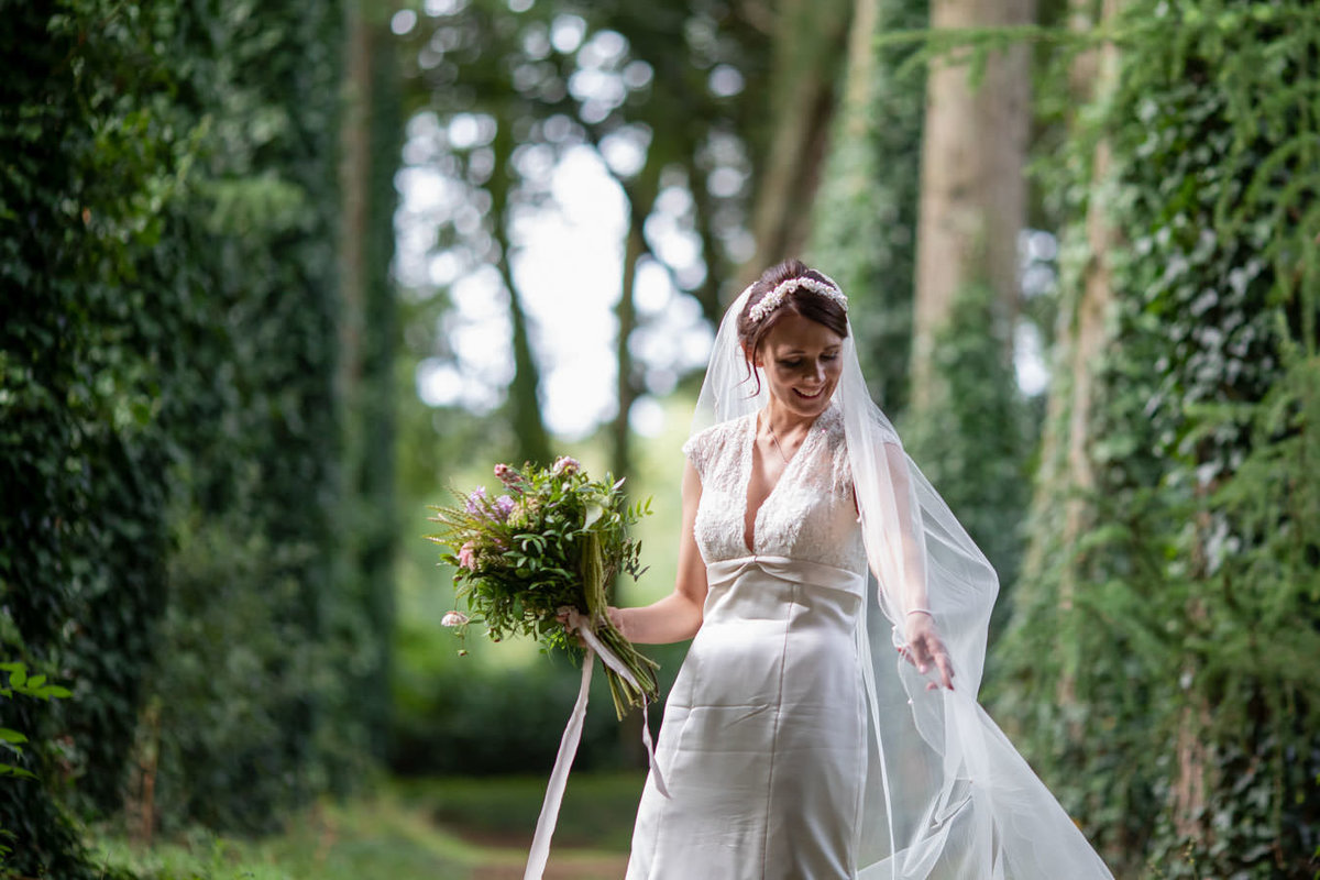 Bride among the trees at Coombe Trenchard Wedding Devon