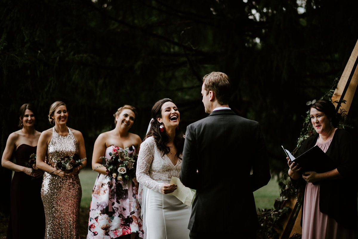 A bride laughs at her groom's vows.