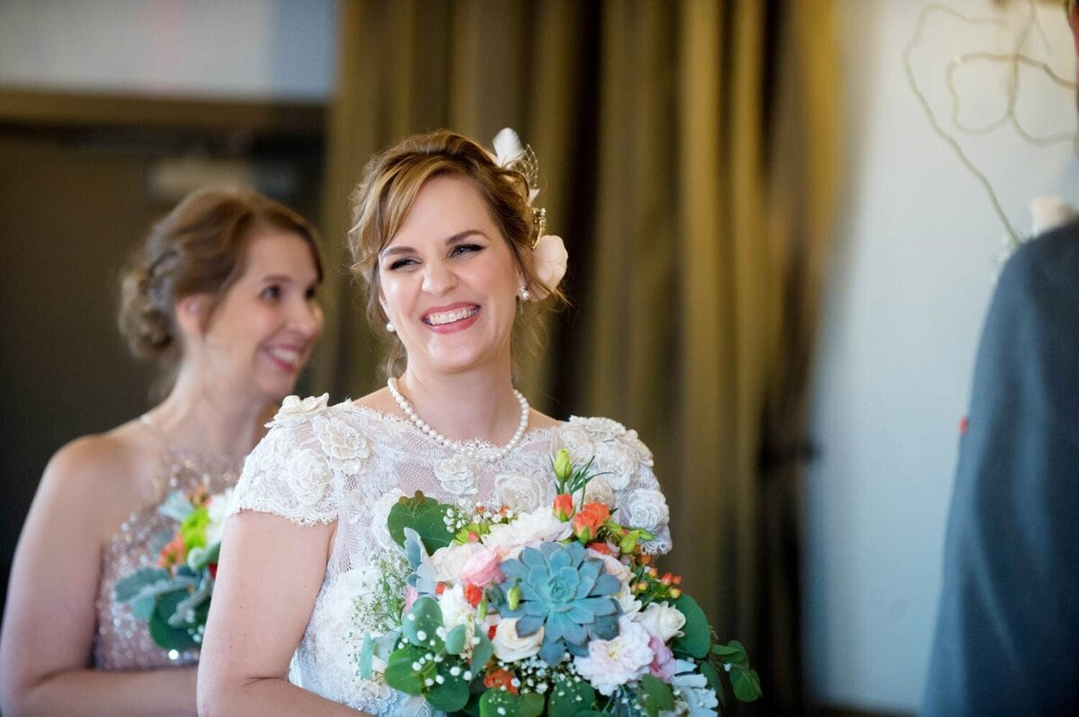 a bride holding a pretty succulent bouquet wearing a vintage dress laughs during the ceremony