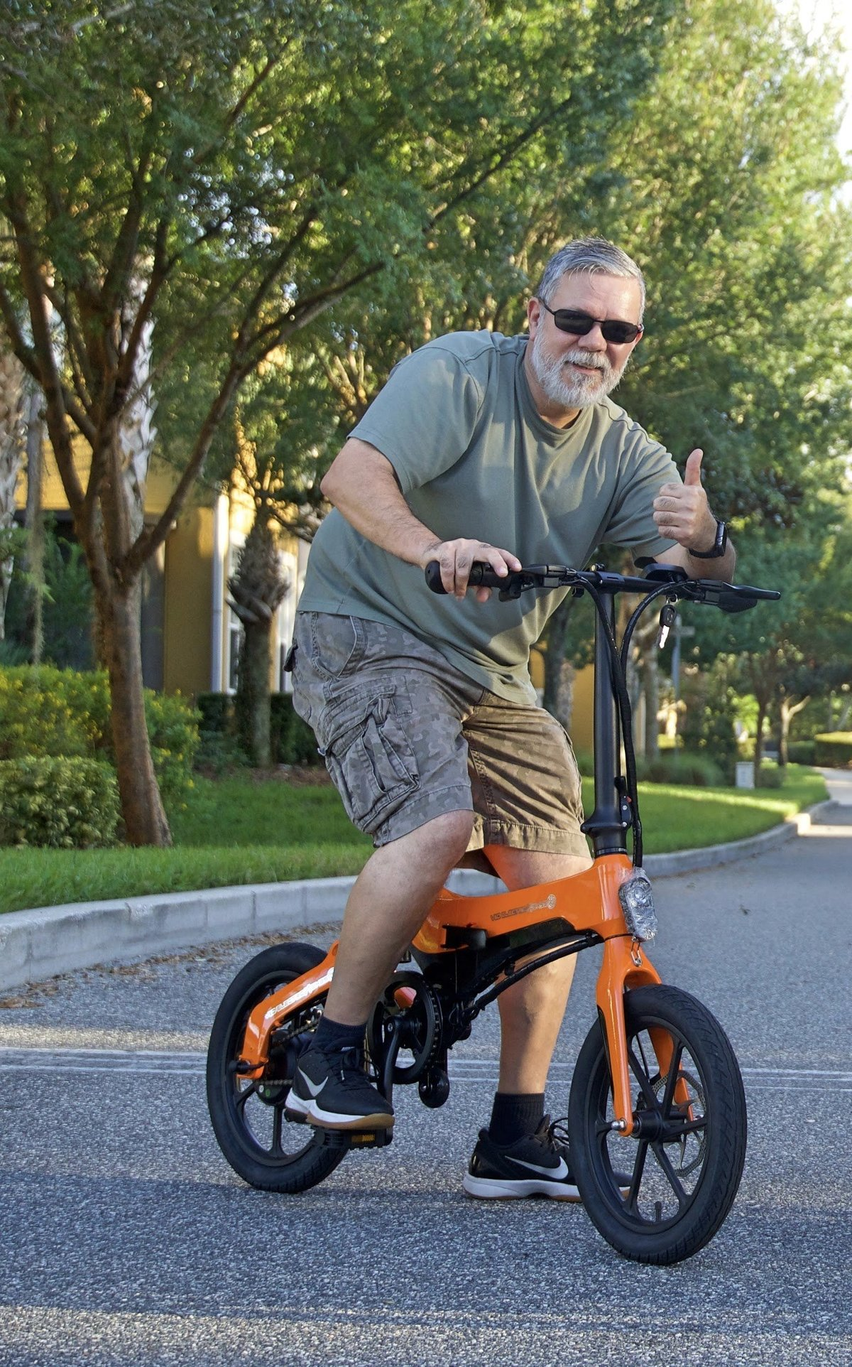 Man giving thumbs up on Orange Go-Bike M4; V&D Electric Bikes