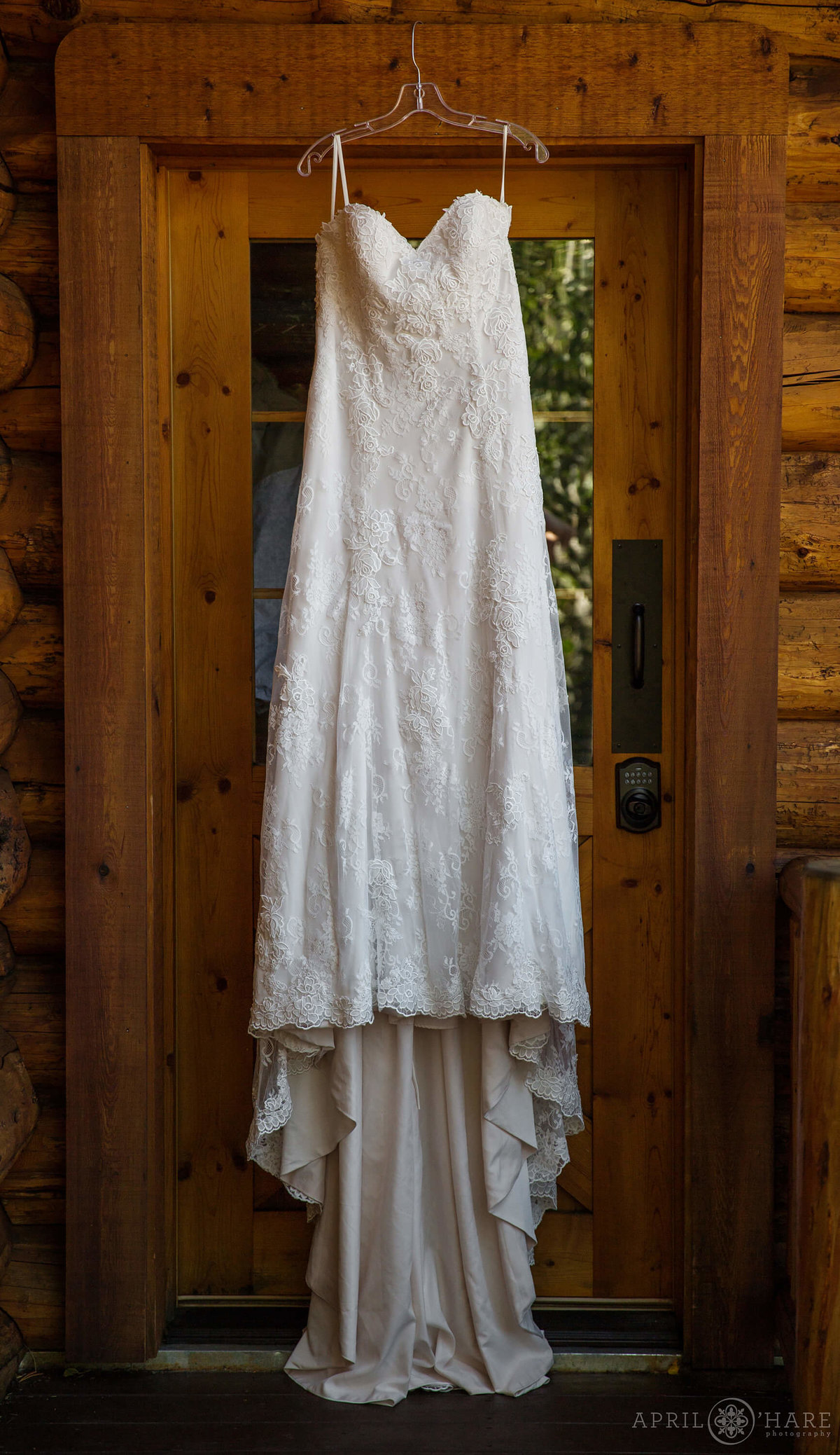 Colorado wedding photographer dress hangs in doorway in Silverthorne CO