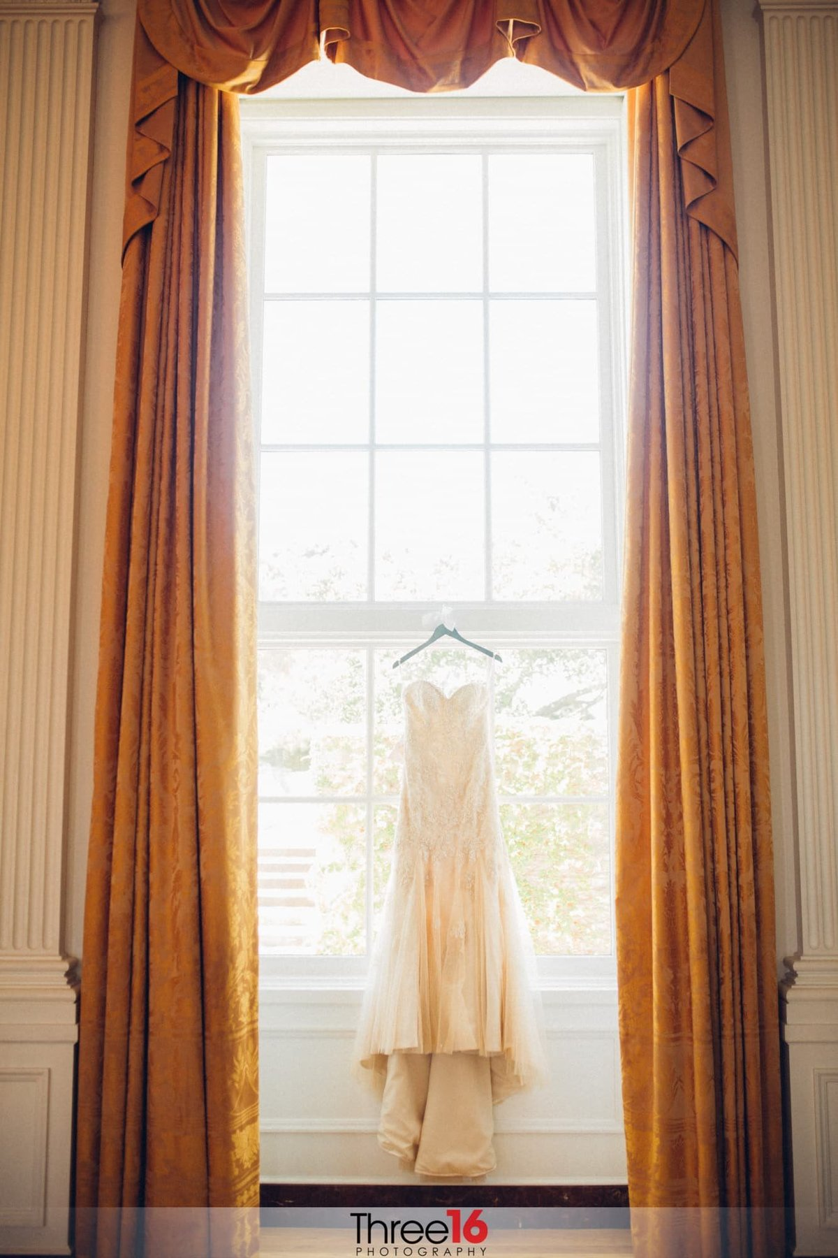 Bride's dress hangs on display in front of a large window