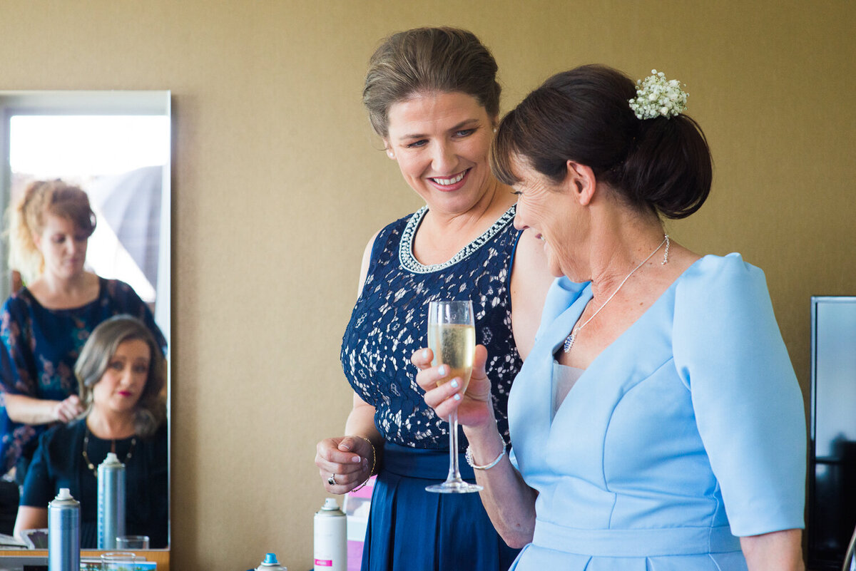 Gay bride looking at Mum in law at wedding preparations