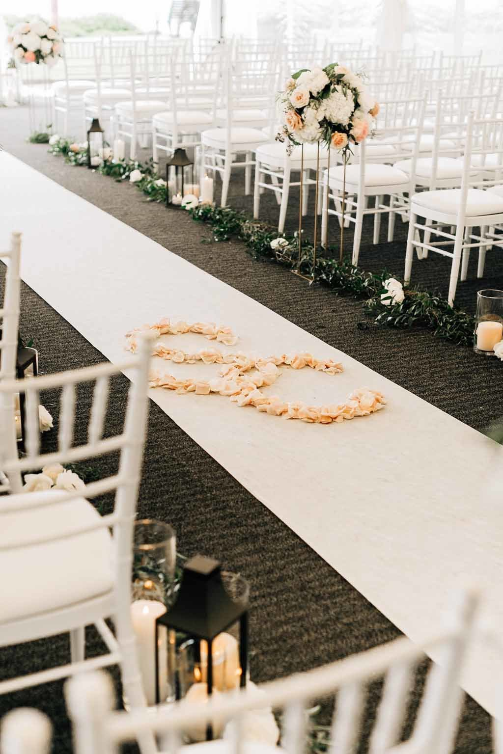 A personal touch of the couples initials in rose petals on the aisle runner designed by Flora Nova Design