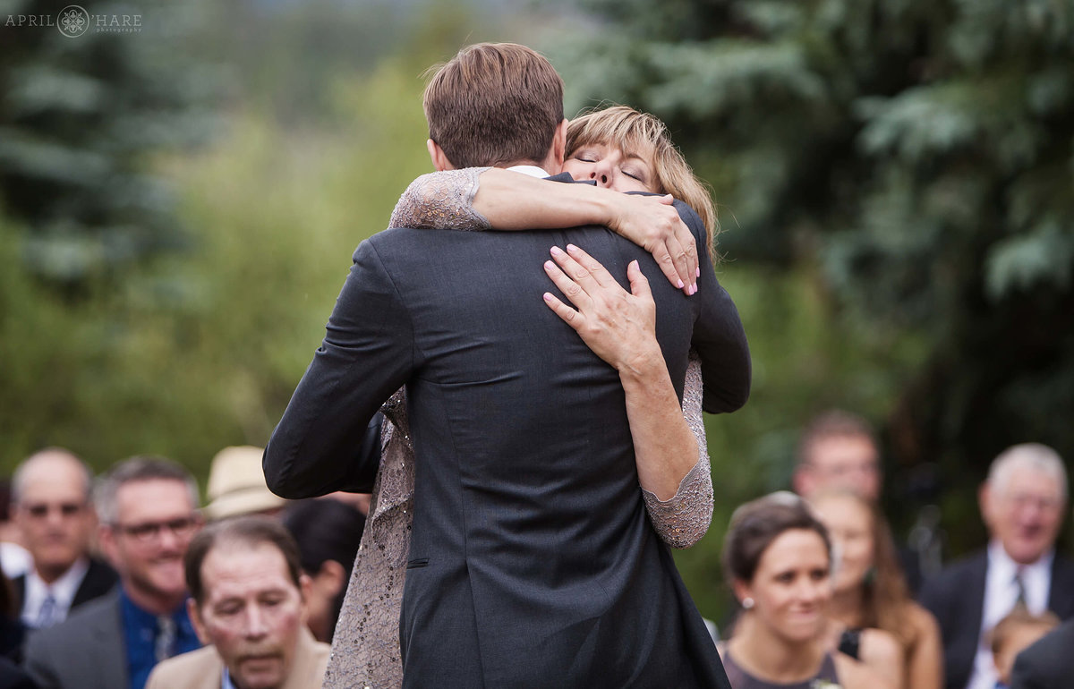 Mom hugs her son at outdoor Colorado mountain wedding at Wedgewood Mountain View Ranch in Pine