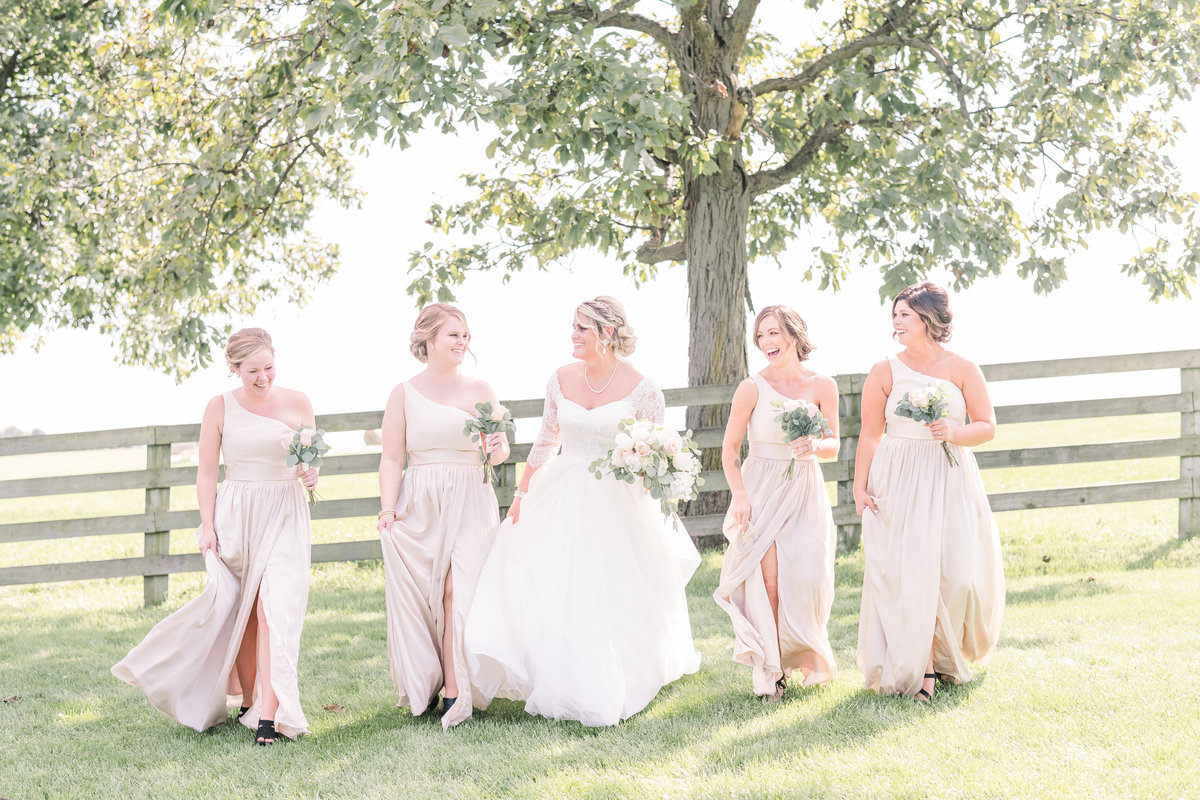 bridesmaids walking and laughing on a wedding day at Ardon Creek winery in Letts, Iowa
