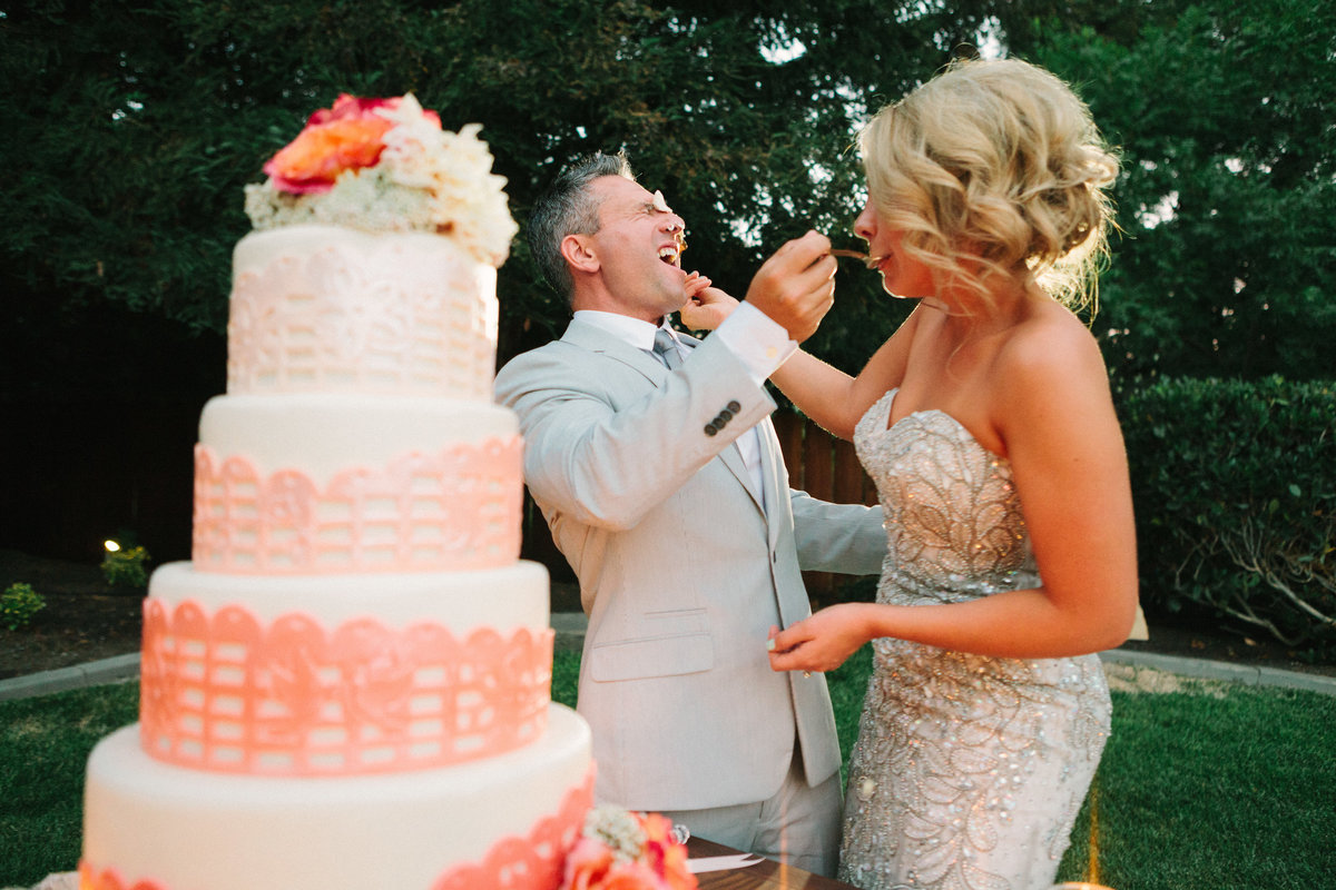 Bride and groom smash cake in each others faces at wedding reception