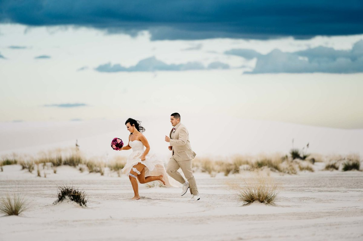 bride and groom running on dunes at white sands