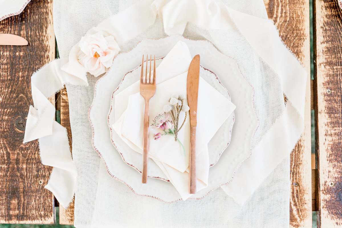 a photo of a place setting on a rustic table with rose gold flatware