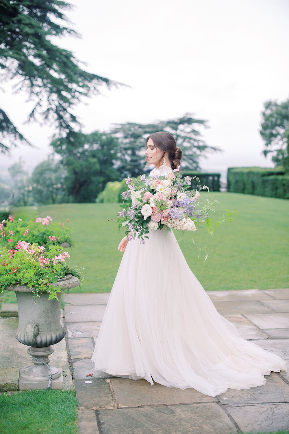 Outdoor bridal portrait with a flowy wedding dress featuring tulle bow straps and a pastel bouquet