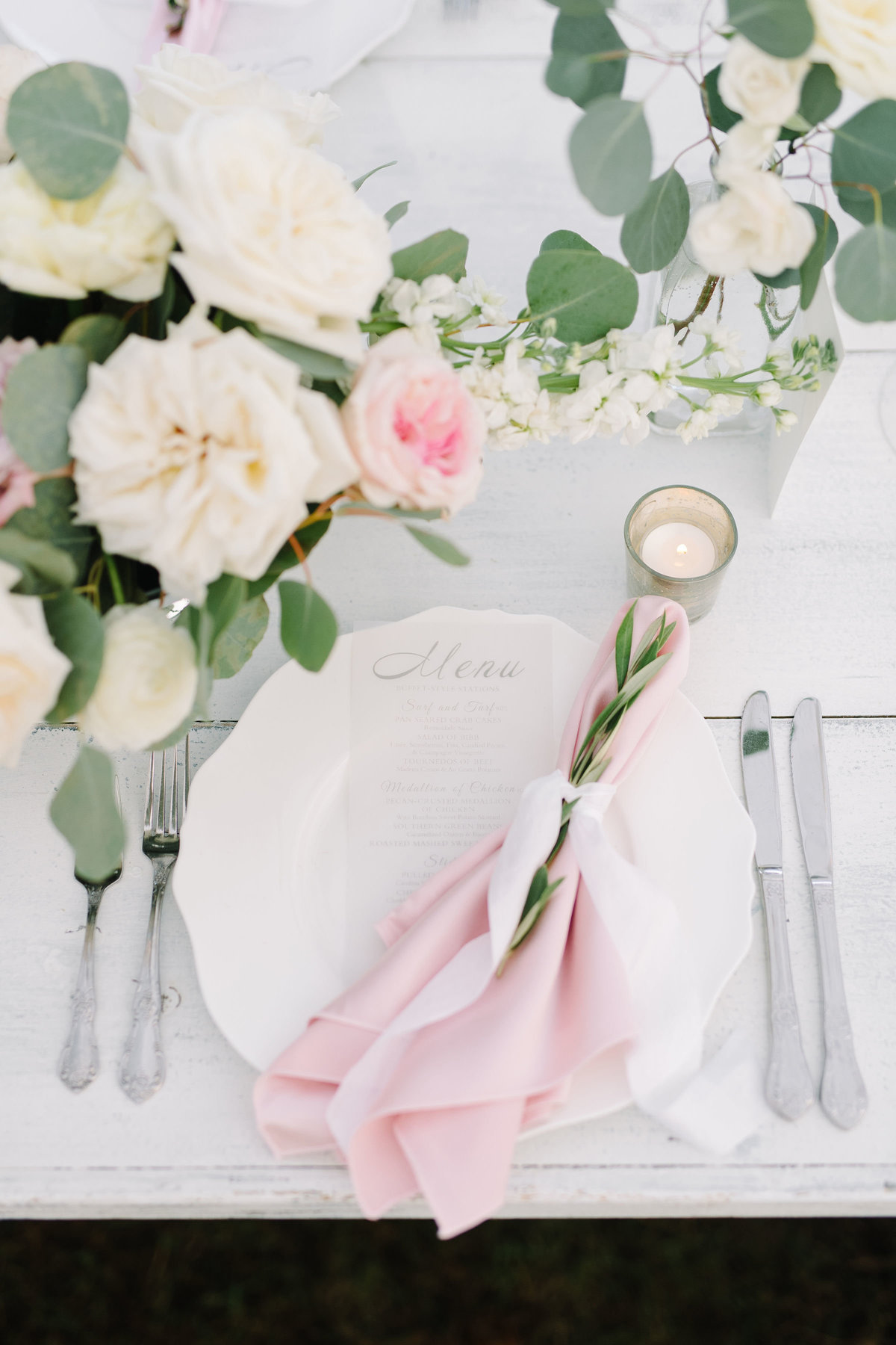 Blush Pink Napkin Fold tied with Ribbon and Sprig of greenery on White Farm Table with Silverware Place Setting