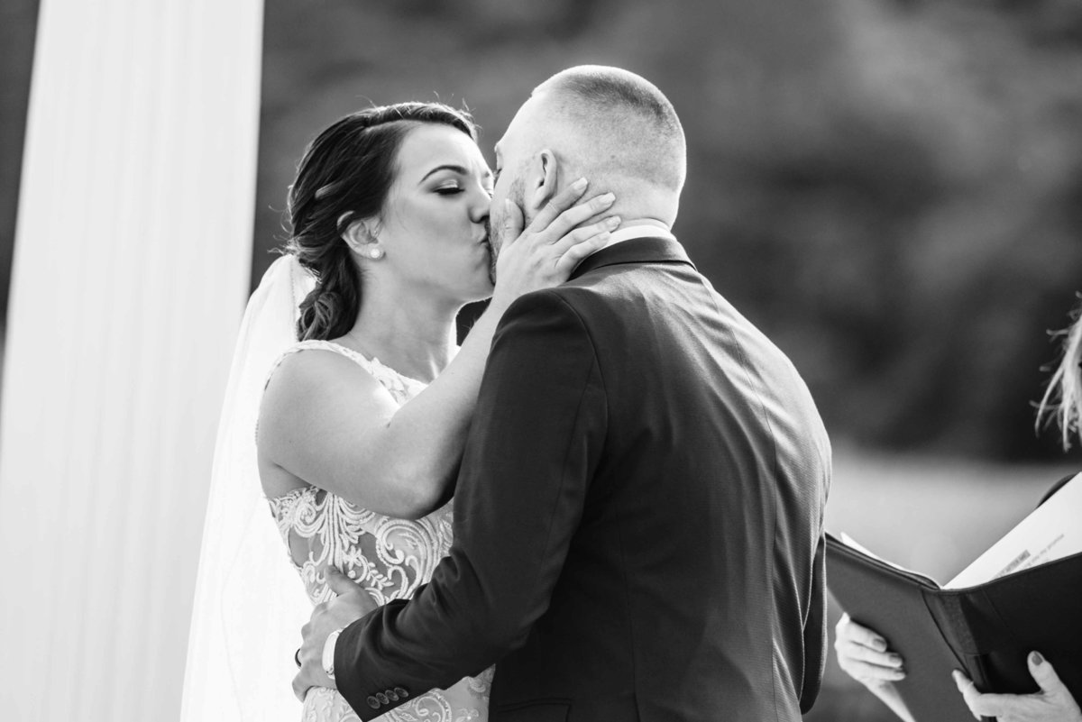 bride kissing groom for the first time after ceremony