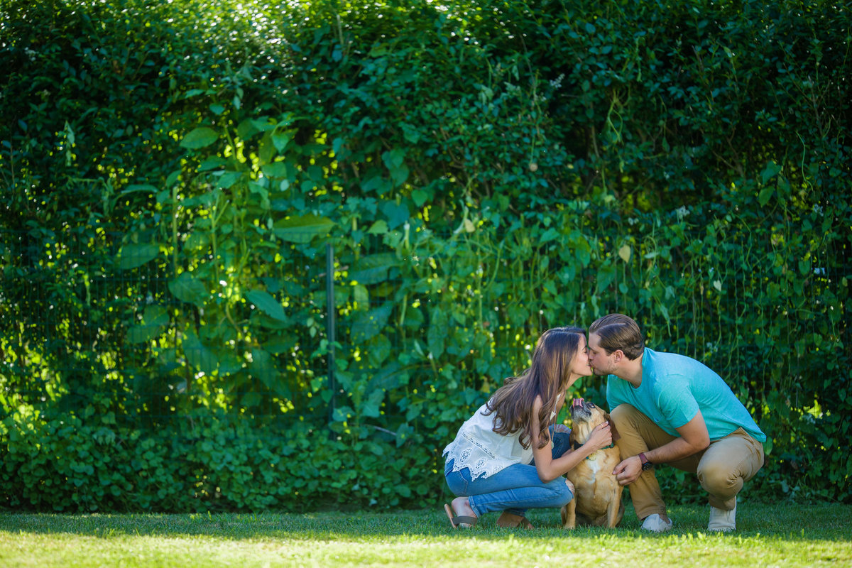 couple with dog sharing a kiss
