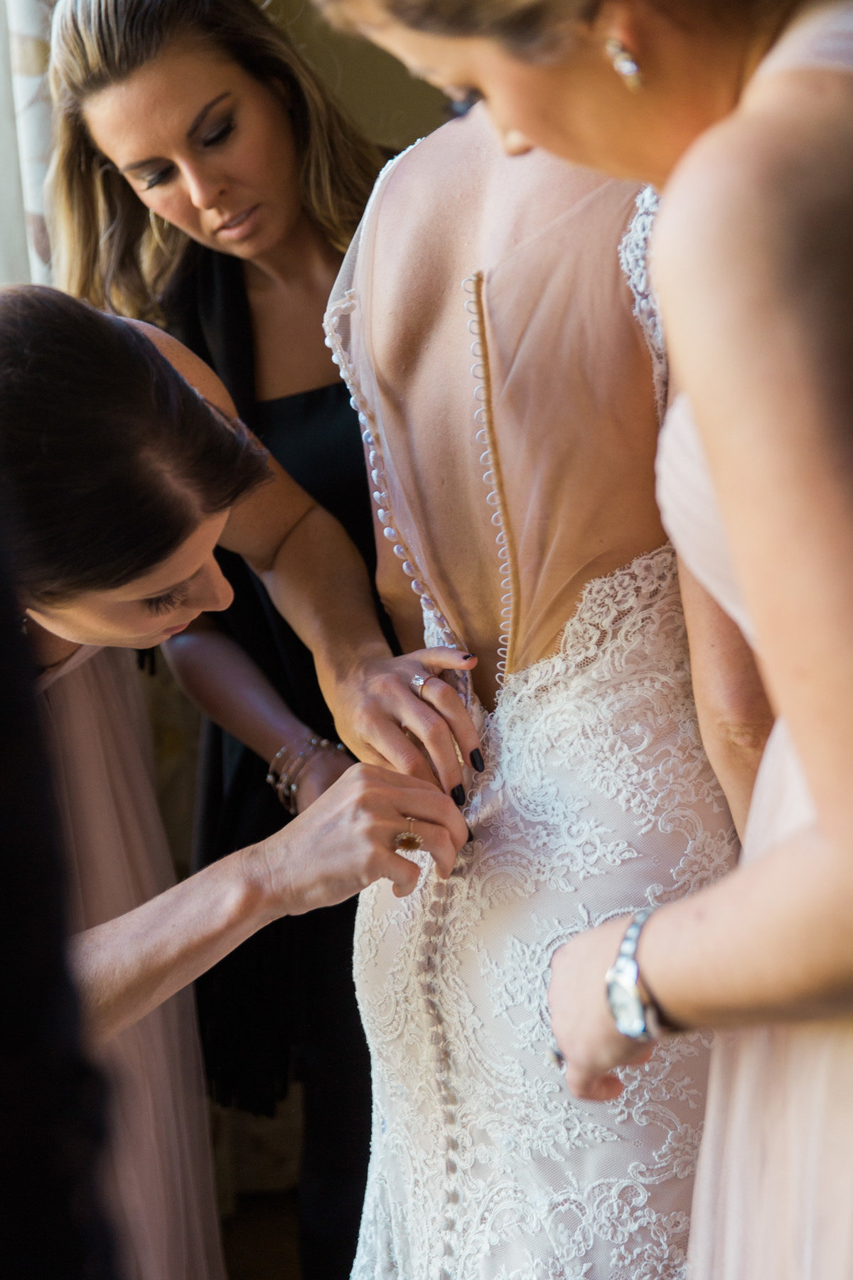Luxury wedding photographer Rebecca Cerasani photographs bridesmaids as they button the brides intricate wedding dress.