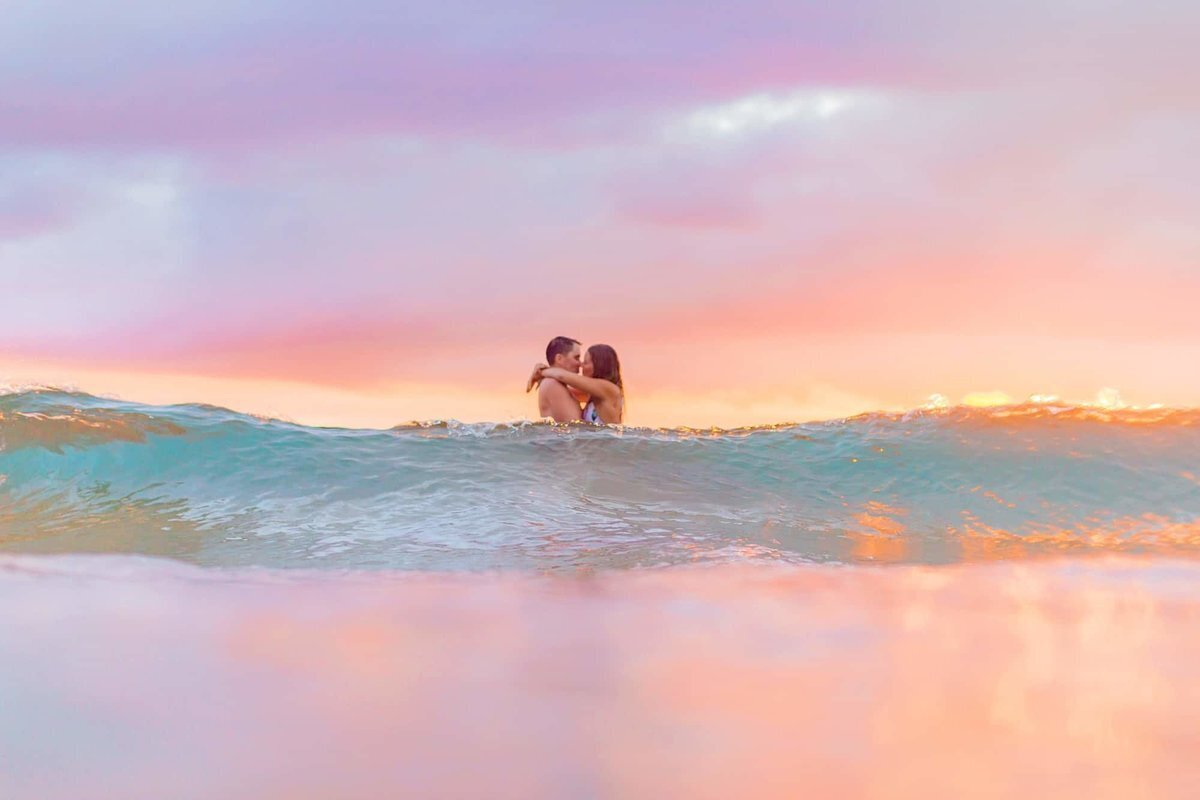 Turquoise Maui waters crash as a couple embraces in the ocean