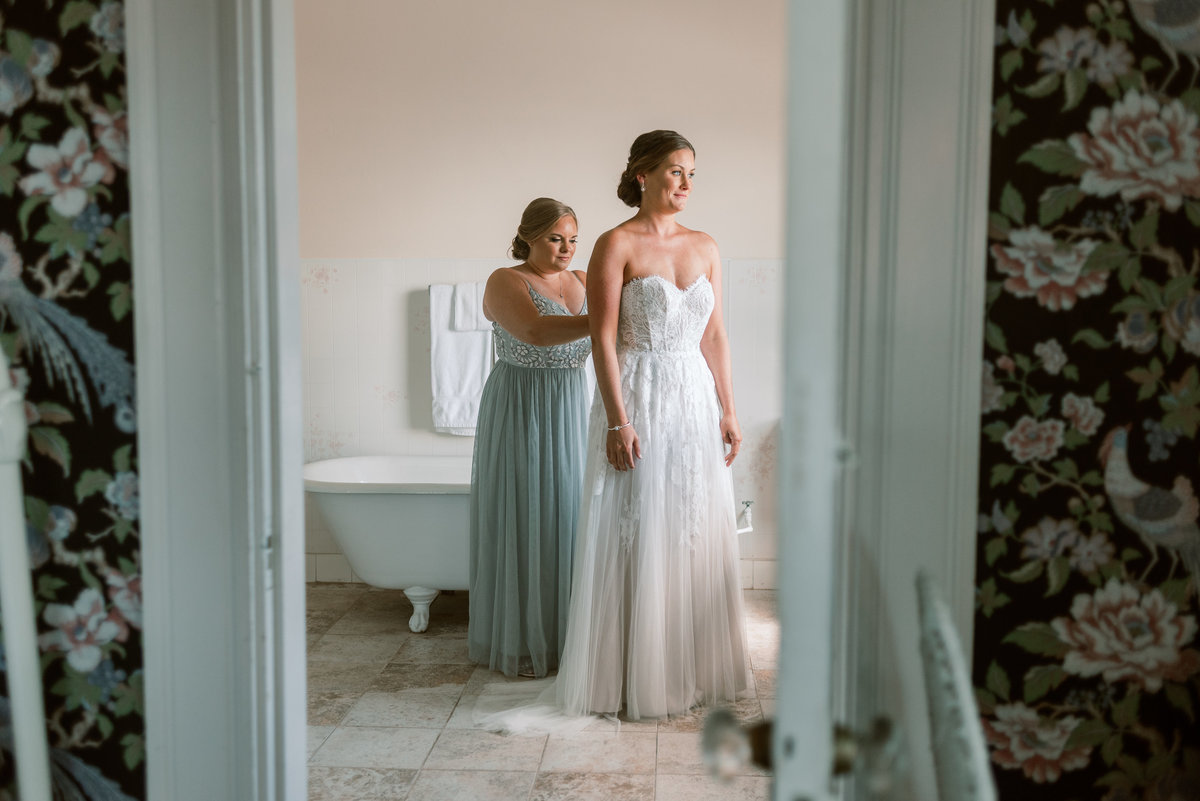 Maid of honor helps bride dress