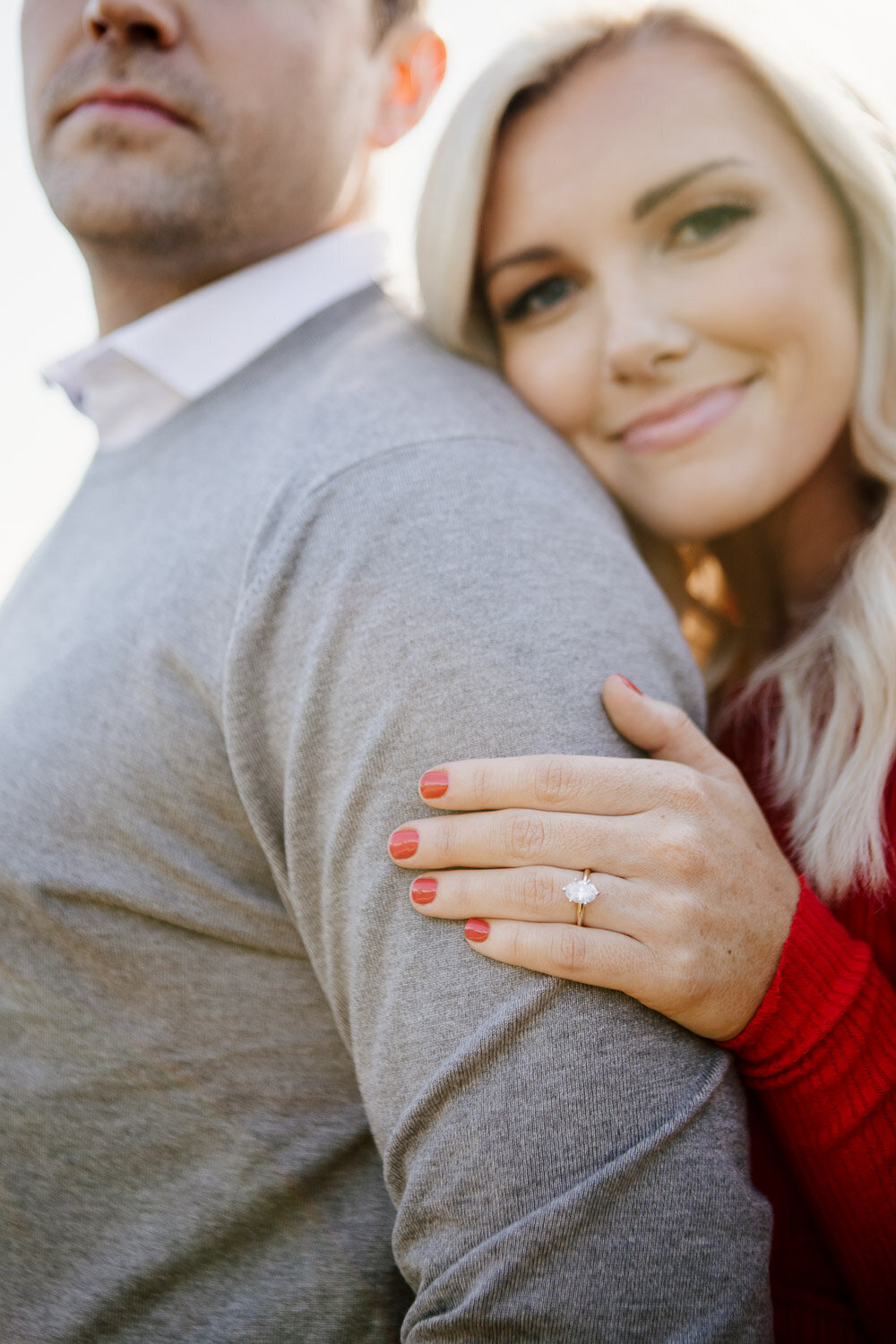 Couple embracing and focusing on engagement ring on woman's hand