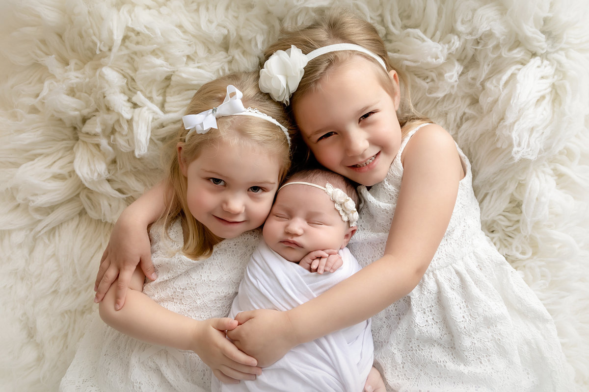 Sisters cuddling their new baby sister