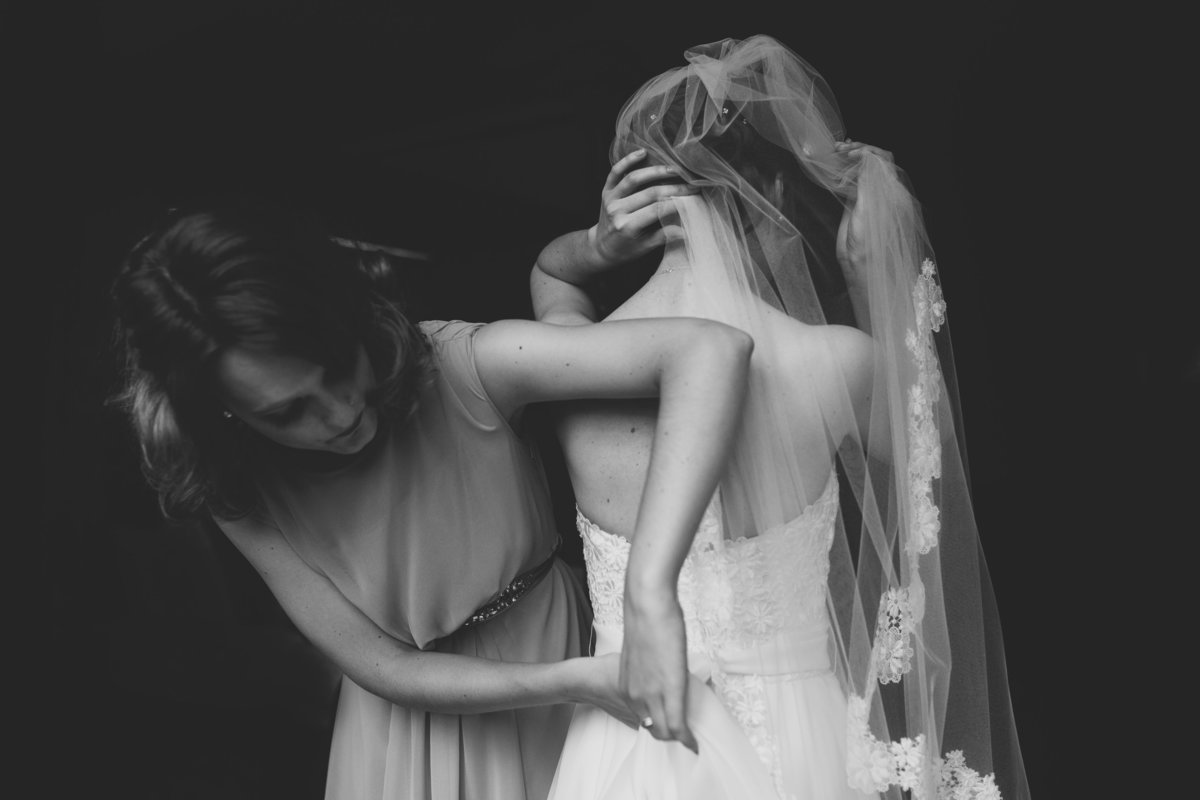 b&w photo of bridesmaid helping bride into wedding dress. clean background at peckforton castle