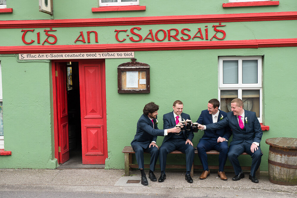 Groom and groomsmen wearing navy suits and pink ties, sitting outside a green and red painted, traditional Irish pub in Ballyferriter, Kerry