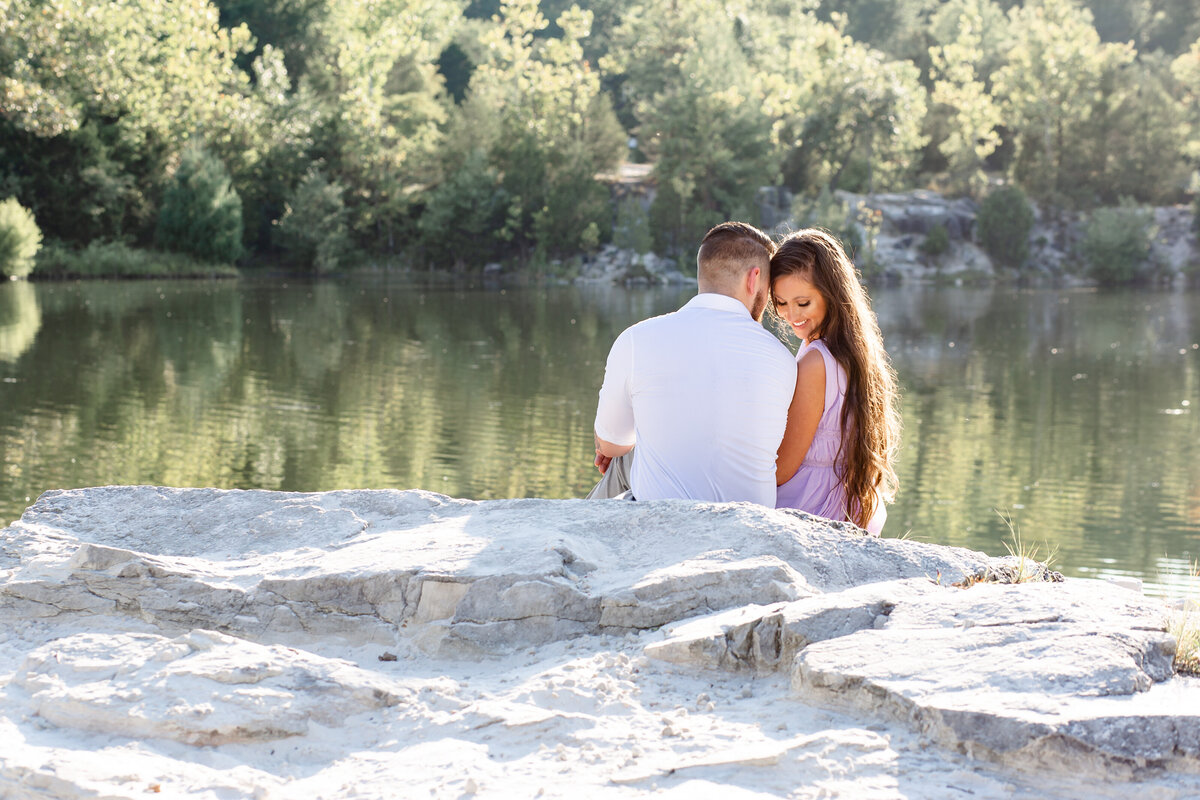 Summer Sunset Romantic Engagement Session in lavender maxi dress couple sitting on rock by water at Klondike Park in St. Louis by Amy Britton Photography Photographer in St. Louis