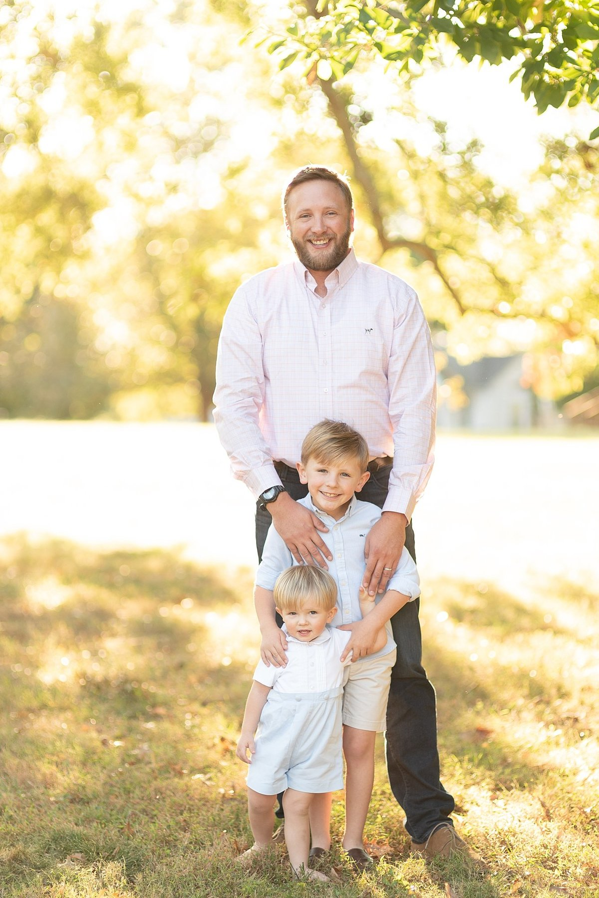 Father and two sons are standing and smiling at the camera with golden hour lighting behind them  for family portraits with Dolly DeLong Photography in Nashville