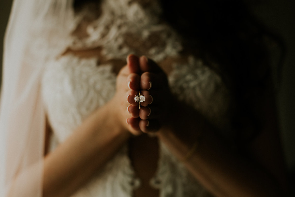 A bride holds her engagement ring in her hand