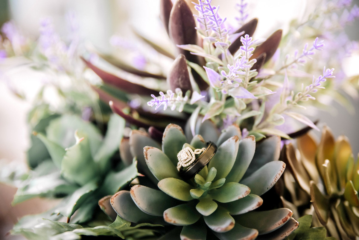 Wedding rings sitting  ontop of succulent bridal bouquet in Pensacola , FL