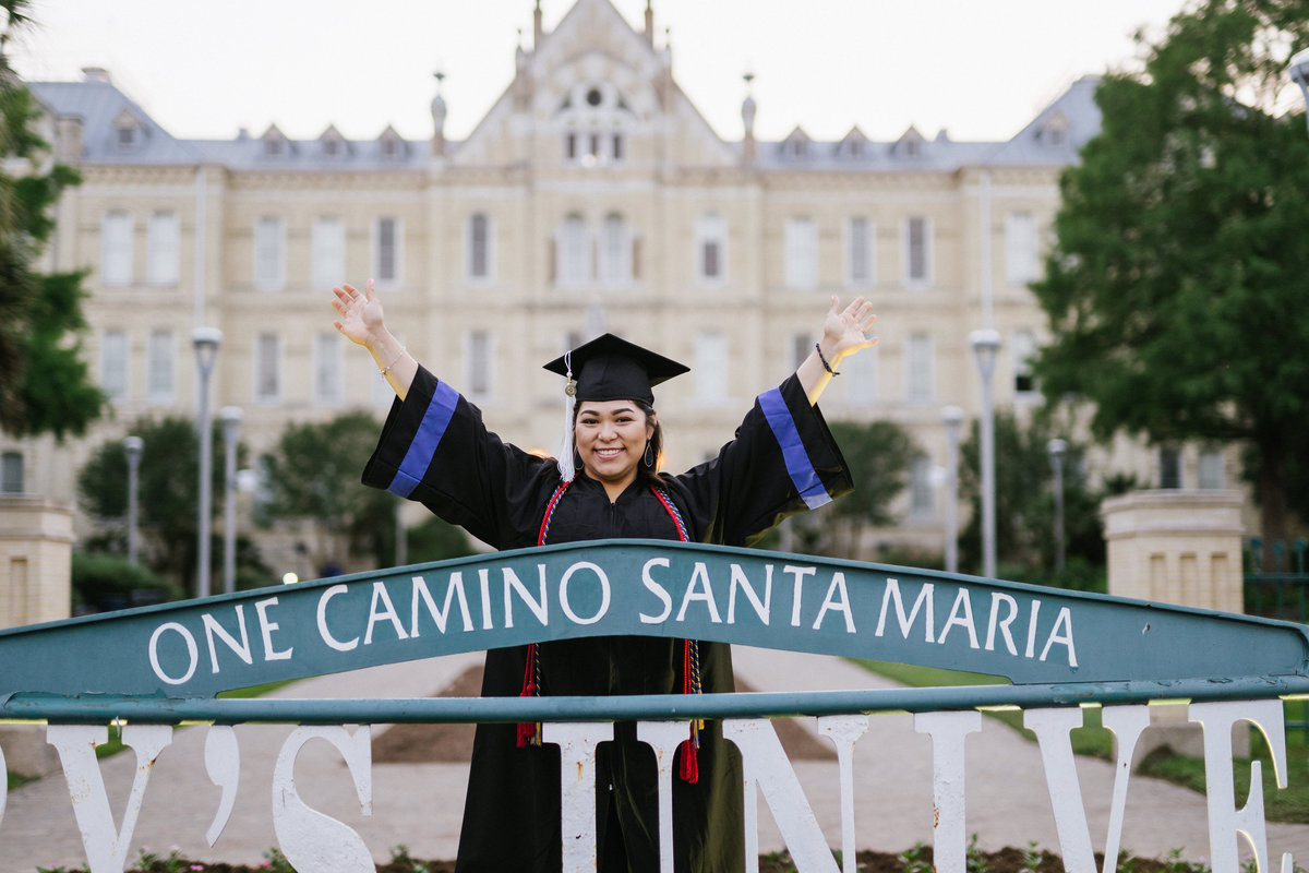 college senior posing at St. Mary's university sign by San Antonio college senior photographer