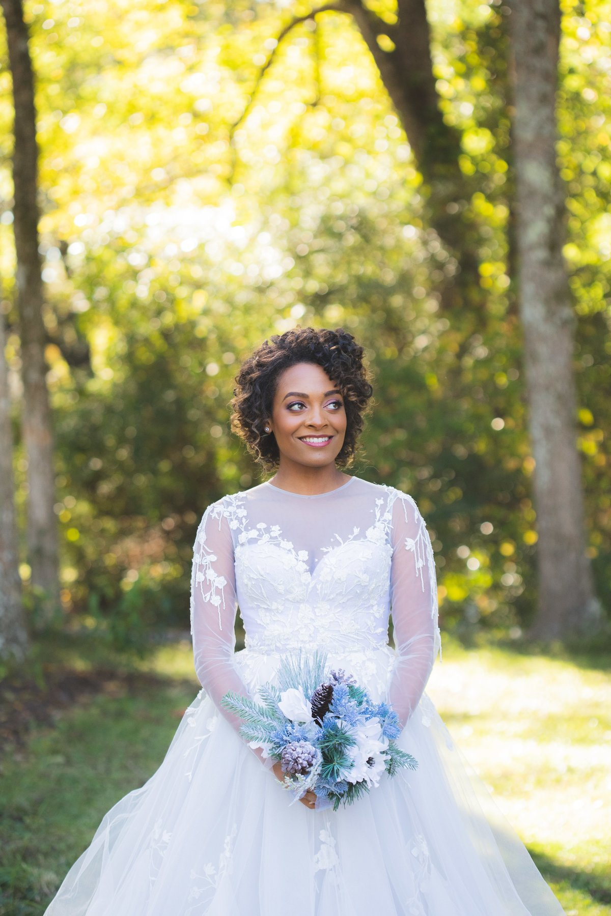 African-american bride posing in forest with blue bouquet