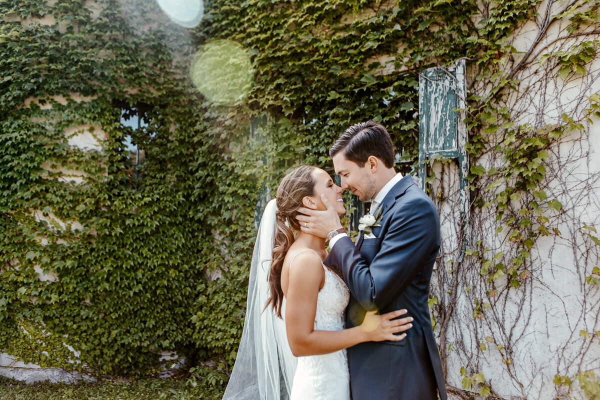Bride & Groom kissing in Knox Farm, New York with foliage building wall